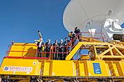 Gasten bij de ALMA-inauguratie op een transportvoertuig