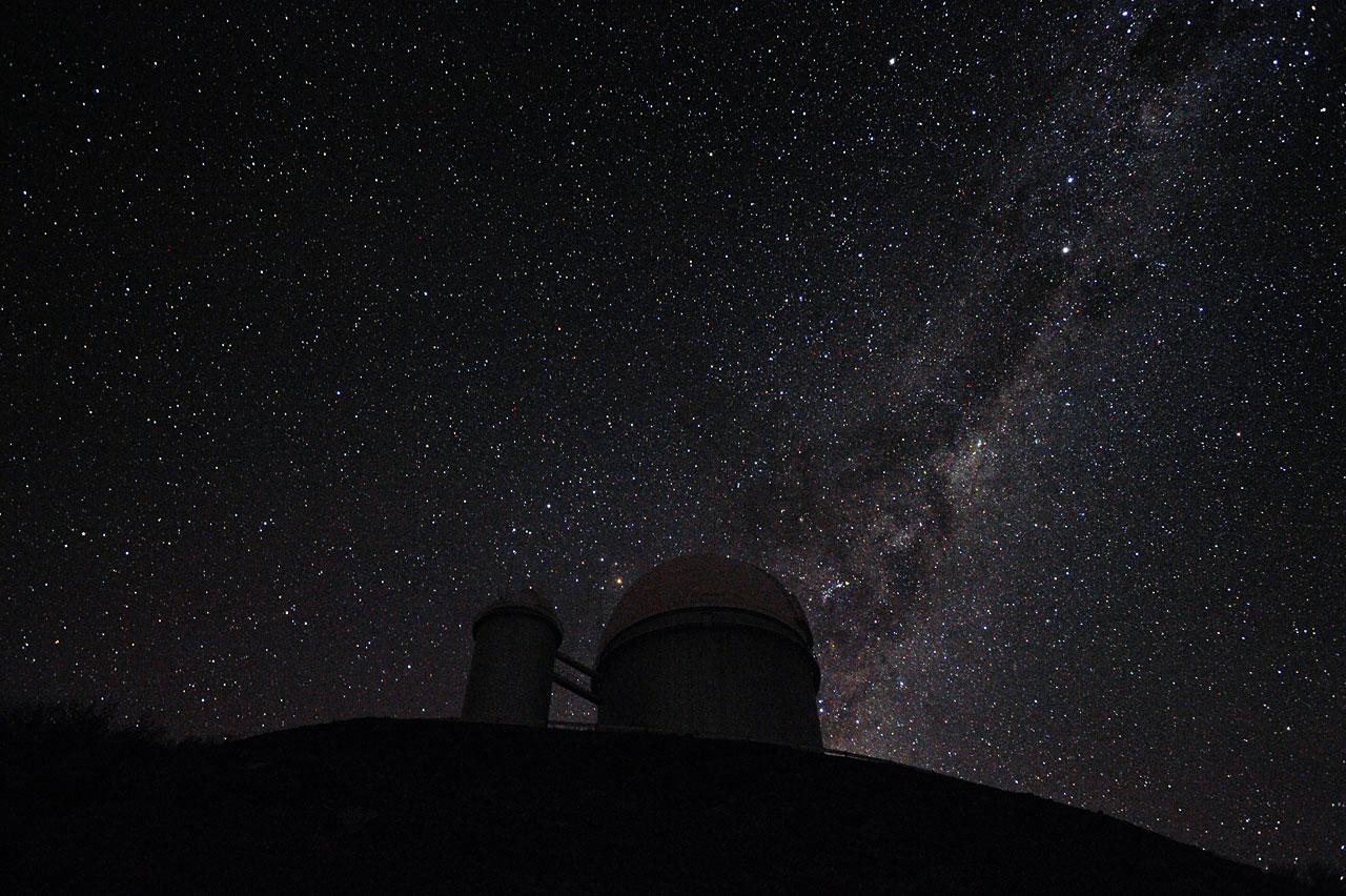 De Melkweg en Alfa en Bèta Centauri achter de 3,6-meter telescoop op La Silla