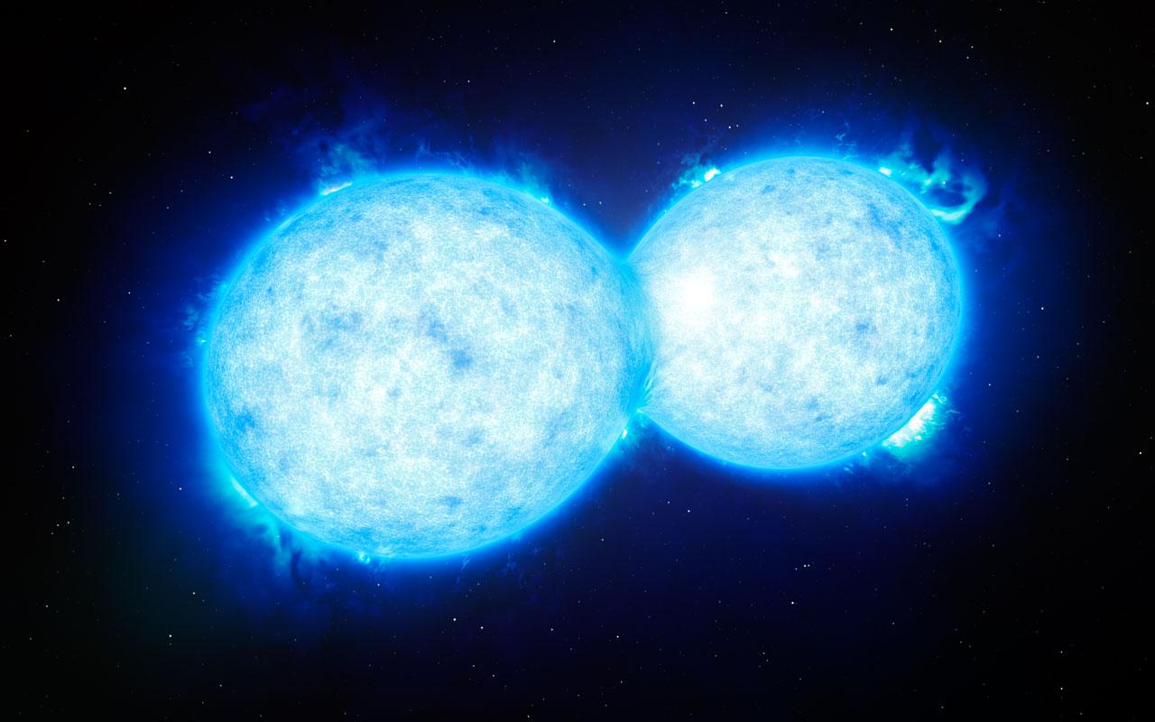 En esta ilustración vemos a VFTS 352 — el sistema estelar doble más caliente y masivo descubierto hasta la fecha donde los dos componentes están en contacto y comparten material. Las dos estrellas de este sistema extremo se encuentran a unos 160.000 años luz de la Tierra, en la Gran Nube de Magallanes. Este intrigante sistema podría ir directo hacia un final dramático, ya sea con la formación de una sola estrella gigante o como un futuro agujero negro binario.