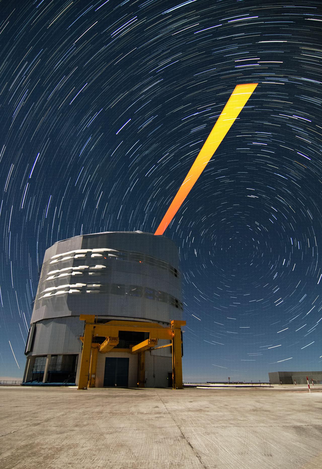De ESO-sterrenwacht op Paranal tegen een achtergrond van stersporen en de VLT-laserbundel