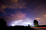 The constellation of Cassiopeia over a thunderstorm