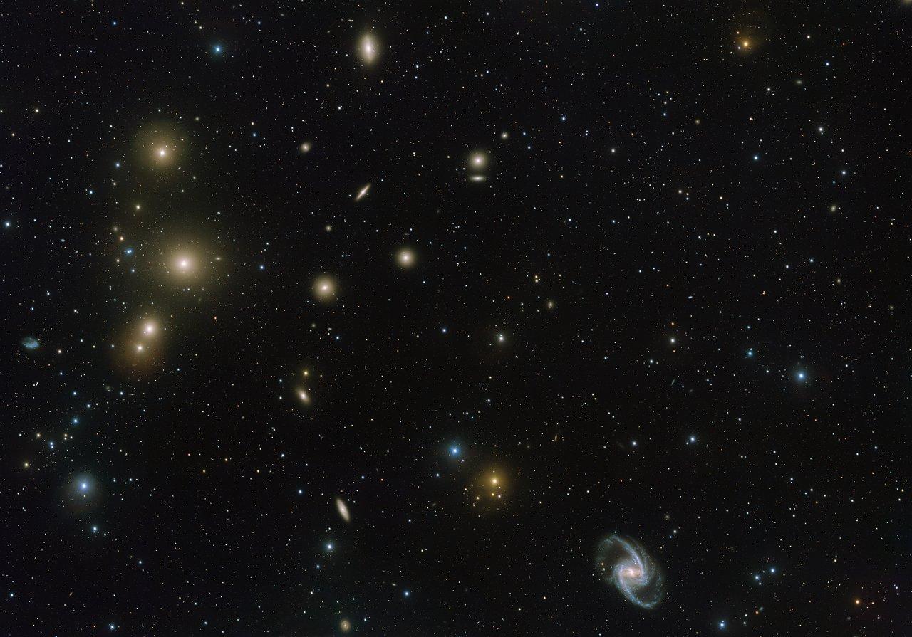 El cúmulo de galaxias de Fornax es uno de los cúmulos de su tipo más cercano a nosotros más allá de nuestro Grupo Local de galaxias. Esta nueva imagen del telescopio de rastreo del VLT muestra la parte central del cúmulo en gran detalle. En la parte inferior derecha vemos la elegante galaxia espiral barrada NGC 1365 y a la izquierda la gran galaxia elíptica NGC 1399.