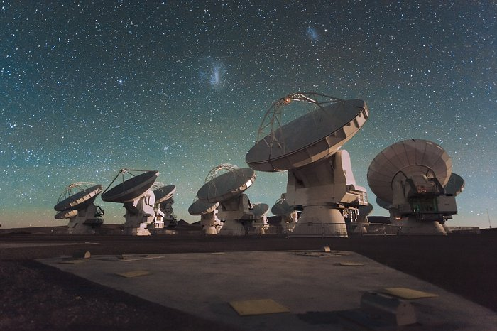 O Atacama Large Millimeter/submillimeter Array (ALMA) à noite, sob as Nuvens de Magalhães