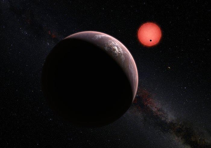 Impressão artística da estrela anã muito fria TRAPPIST-1 e dos seus três planetas