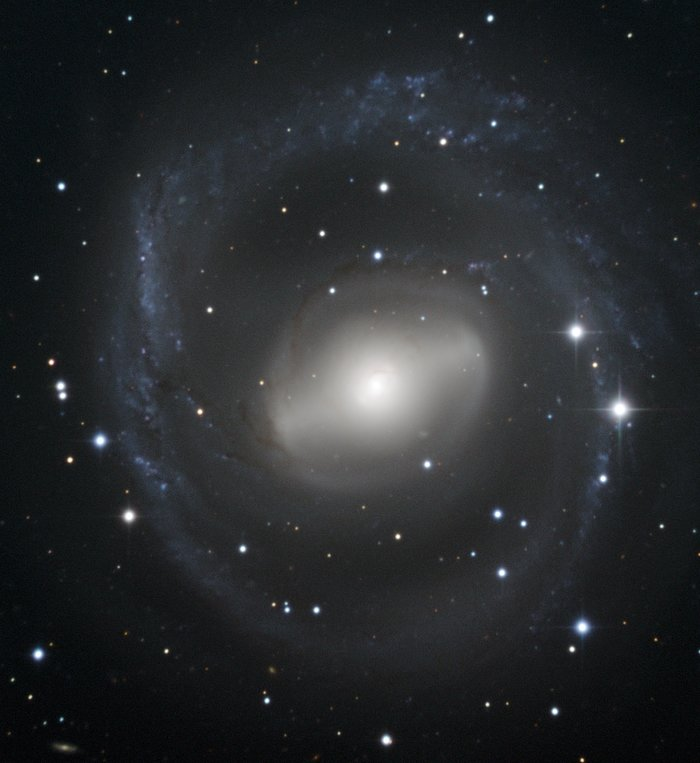 Barred spiral galaxy swirls in the night sky