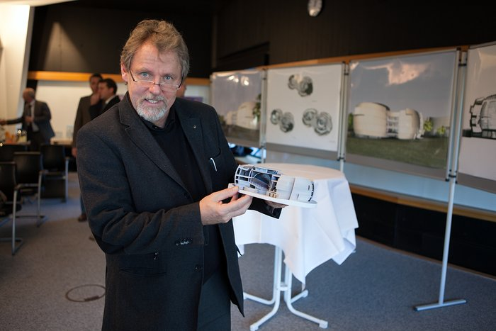 Architect of the ESO Supernova Planetarium & Visitor Centre showing a model of the planned building