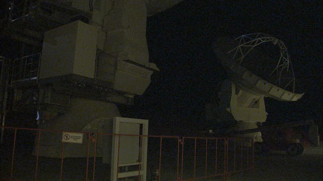 An ALMA antenna moves in the night