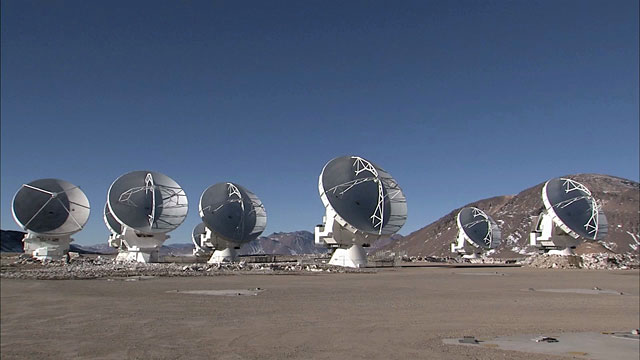 Pan over ALMA array of antennas on Chajnantor as they move in unison
